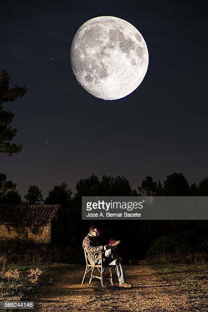 Seated man reading a book in the moonlight