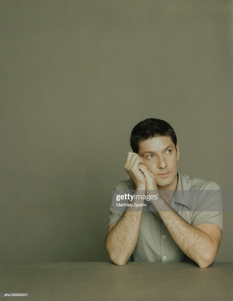 Seated man with elbows on table, leaning head against clasped hands, portrait : Stockfoto