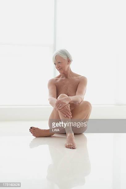 seated nude mature woman - senioren aktfotos stock-fotos und bilder