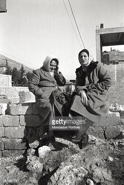 Seated on a low wall two women talking San Giovanni Rotondo Italy