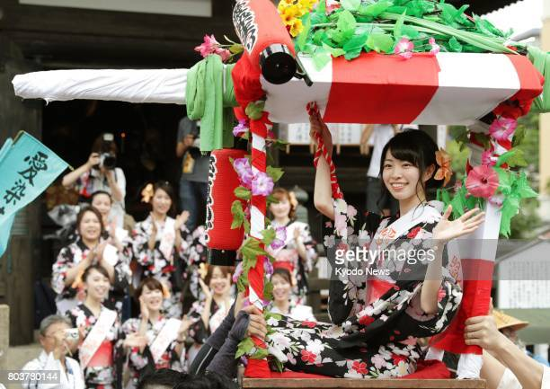 Seated on a palanquin a woman wearing a Japanese summer kimono is carried through the seats of Osaka on June 30 during a local summer festival There...