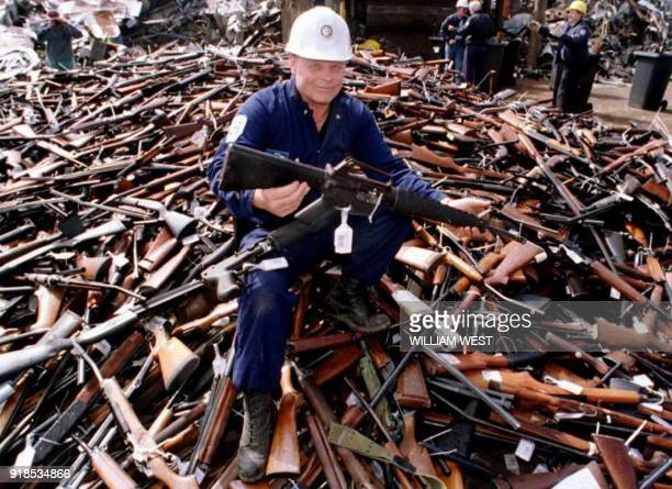 Norm Legg a project supervisor with a local security firm holds up an armalite rifle which is similar to the one used in the Port Arthur massacre and...