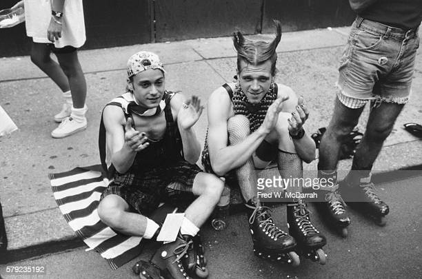 Seated on a sidewalk curb rollerbladers applaud during the annual Gay Pride Day March New York New York June 30 1991