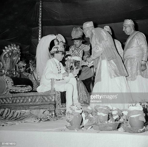 Seated on Nepal's famed cobra throne King Mahendra admires his plumed $1000 crown in a vanity mirror as Queen Devi adjusts her royal headgear Priests...