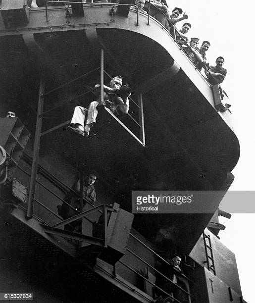 Seated on the framework below the USS Lexington flight deck Comdr Edward Steichen takes photographs with a K20 aerial camera November or December...