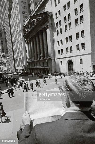 Seated on the steps of Subtreasury Building in Lower Manhattan an office worker reads Wall Street Journal May 29th across the street from the New...
