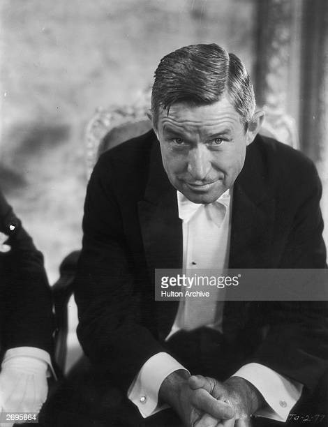 Seated portrait of American actor and humorist Will Rogers leaning forward and wearing a tuxedo