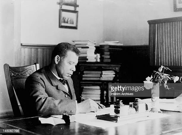 Seated portrait of American educator economist and industrialist Booker T Washington founder of the Tuskegee Institute in Alabama at his desk early...