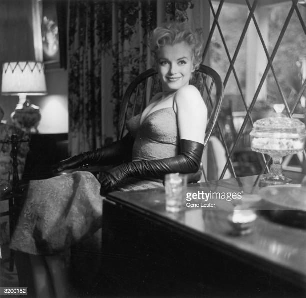 Seated portrait of Marilyn Monroe smiling sitting on a chair by a window
