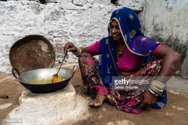seated portrait of one mid adult female gujar villager stirring the food she is cooking in a pan on an open hearth, in bright blue and pink traditional clothing with many bracelets against white wall, pushkar, rajasthan, india (model release) - james strachan stock pictures, royalty-free photos & images