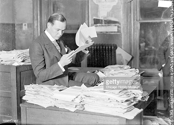 Seated portrait of silent film star Charles Ray seated at a desk and reading manuscripts in the Chicago Daily News scenario department Chicago IL...