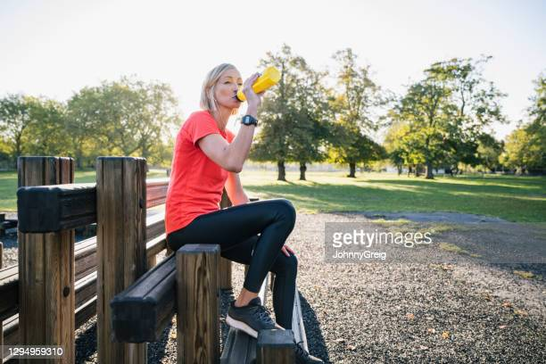 seated sportswoman in early 50s taking a break after workout - clapham common stock pictures, royalty-free photos & images