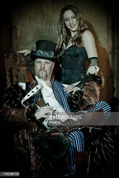 Seated Steampunk man with striped suit top hat goggles and large coat and woman in corset with feathers in her hair Los Angeles USA 2011