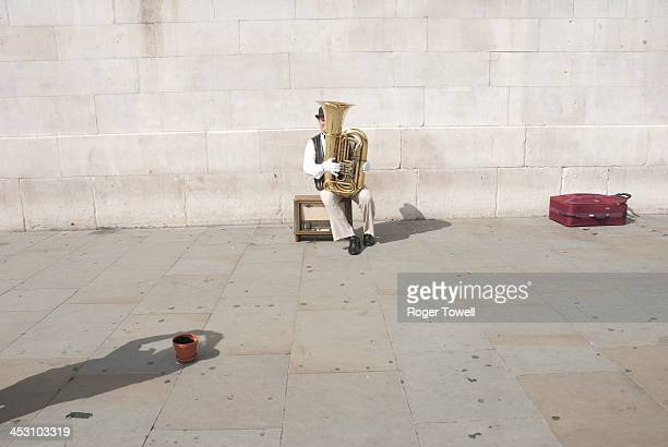 CONTENT] A seated Street Entertainer playng a musical instrument in Trafalgar Square central London A shadow of one of the audience is visible in the...