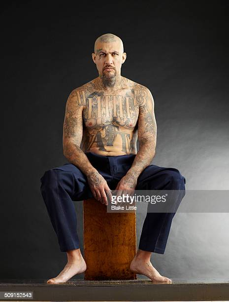 Seated tattooed man in studio.