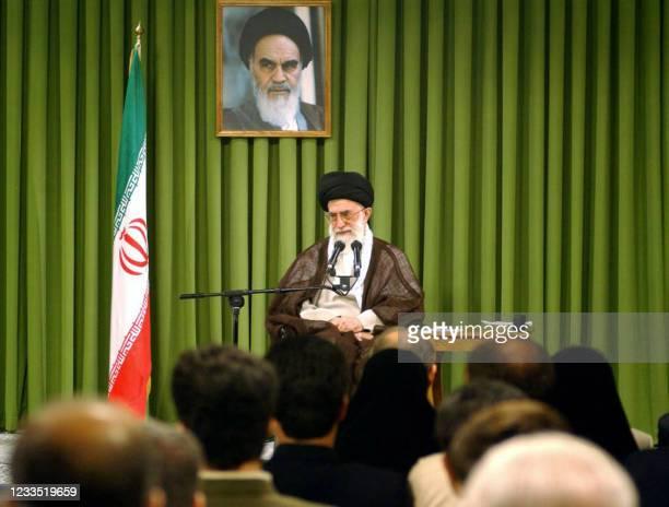 Seated under a portrait of his predecessor Ayatollah Ruhollah Khomeini, Iran's supreme leader Ayatollah Ali Khamenei addresses the staff of the...