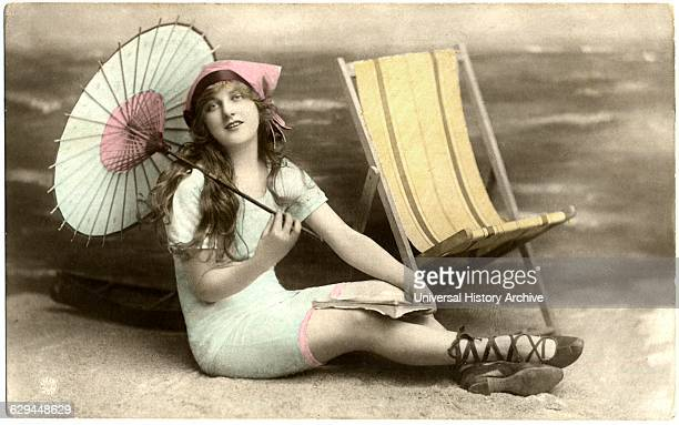 Seated Woman in Blue Swim Dress Holding Parasol next to Beach Chair, circa early 1900's.
