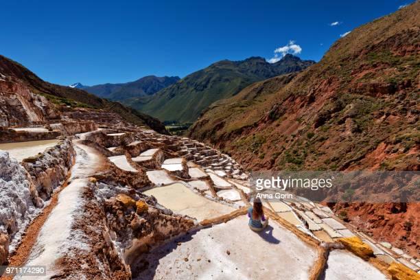 Seated woman looking out over Salinas de Maras salt evaporation ponds in Cusco region, Peru