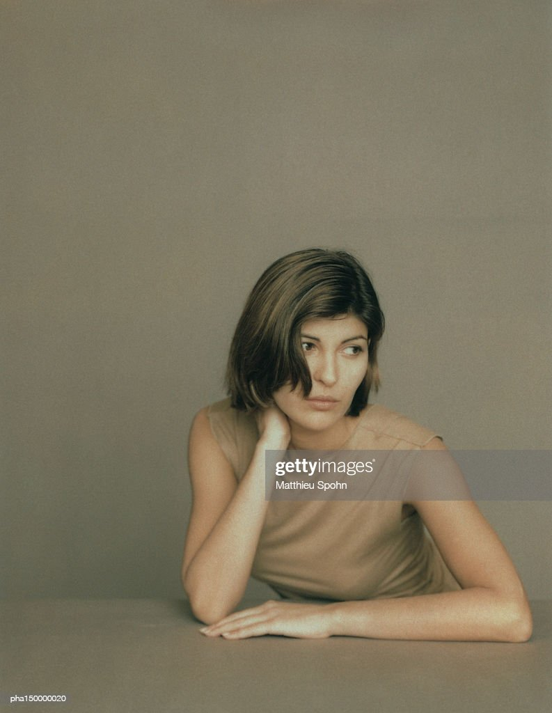 Seated woman with elbows on table, leaning forward with hand behind neck, portrait : Stockfoto