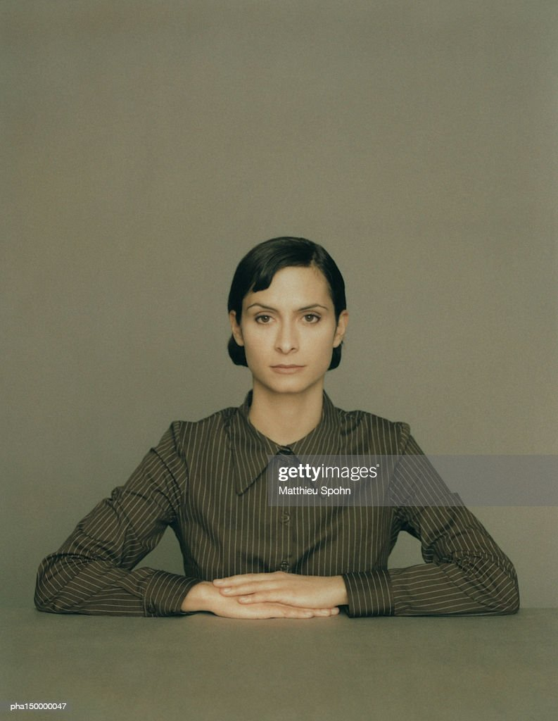 Seated woman with hands crossed on table, portrait : Stockfoto