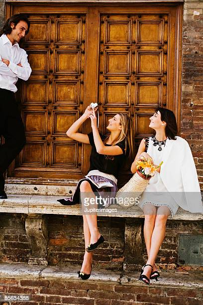 Seated young adults taking a picture , Siena , Italy