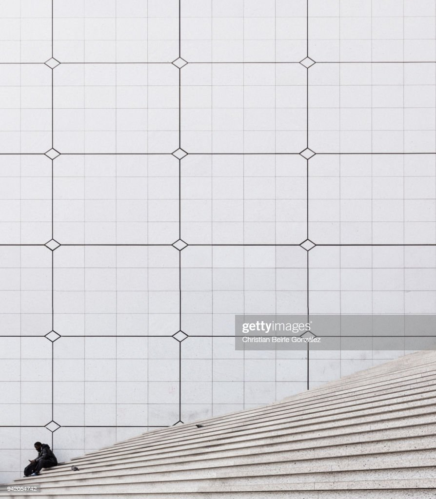 A seating man taking a relaxation break at the staircase of the Grande Arche at La Défense, Paris : Foto de stock