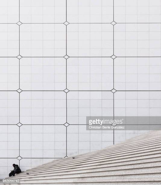 a seating man taking a relaxation break at the staircase of the grande arche at la défense, paris - christian beirle gonzález fotografías e imágenes de stock