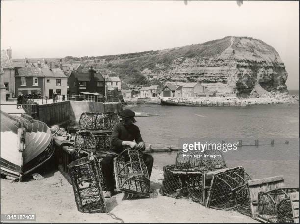 Seaton Garth, Staithes, Hinderwell, Scarborough, North Yorkshire, 1930s. A man mending lobster pots on the beach beside Seaton Garth at Staithes with...