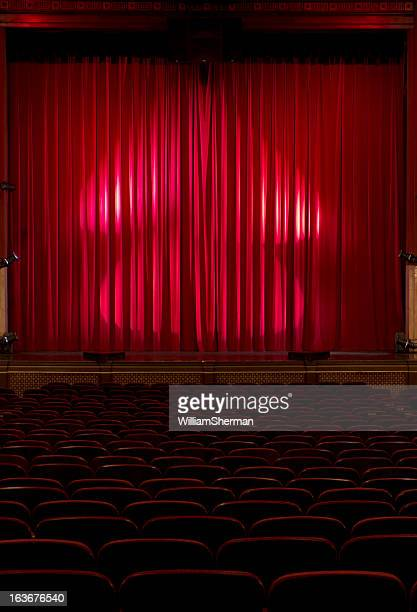Seats In a Darkened Theater with Red Velvet Curtains
