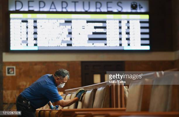 Seats in a waiting area are cleaned by a member of the custodial staff at Union Station on March 13, 2020 in Los Angeles, California. L.A. Metro...