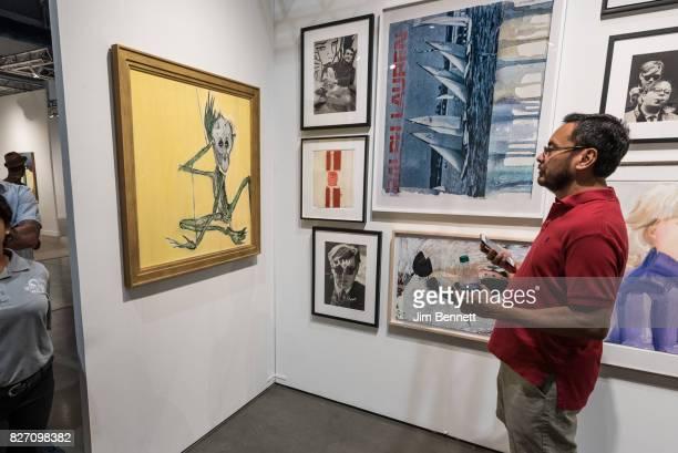 Seattle Art Fair attendee examines the work Fistula by Kurt Cobain at CenturyLink Field on August 6 2017 in Seattle Washington