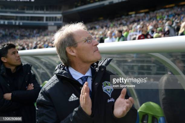 Seattle head coach Brian Schmetzer applauds as the Sounders 2019 Championship banner if unveiled before their opening MLS match between the Chicago...