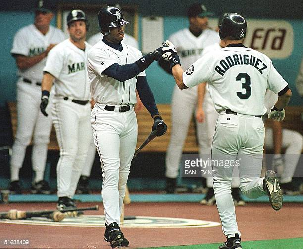Seattle Mariner Alex Rodriguez is congratulated by Ken Griffey Jr after Rodriguez hit his 31st homer of the season during first inning play against...