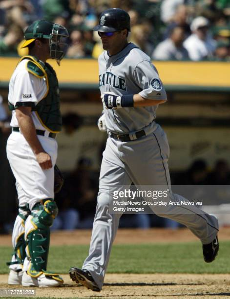 Seattle Mariners' # 30 Russell Branyan crosses home plate in front of Oakland Athletics catcher Landon Powell after Branyan hit a solo homerun in the...
