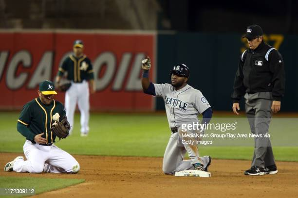 Seattle Mariners' Abraham Almonte points out skywards after sliding safe at second as Oakland Athletics' Jed Lowrie bobbles the ball in the fifth...