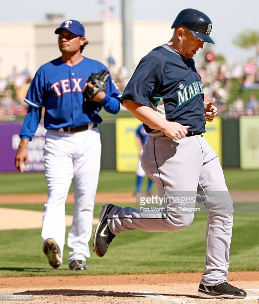 Seattle Mariners Chris Shelton crosses the plate to score a run as Texas Rangers pitcher Vicente Padilla looks on in the first inning during a Texas...
