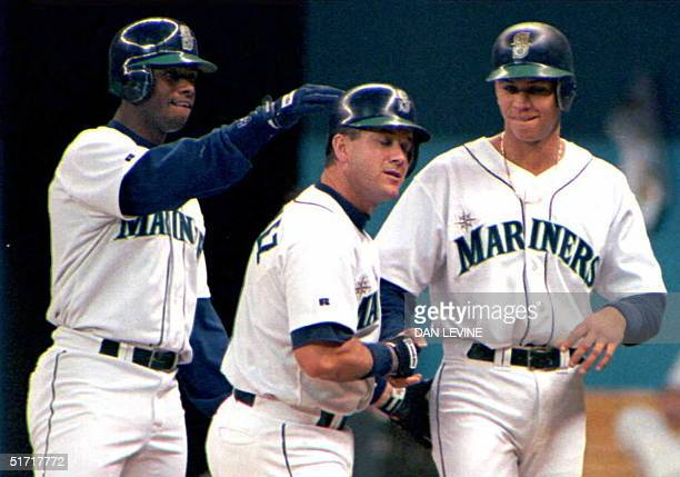Seattle Mariners' Edgar Martinez grimaces after he is congratulated by teammates Ken Griffey Jr and Alex Rodriguez after Martinez hit a first inning...