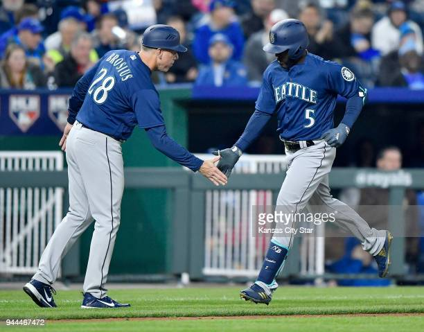 Seattle Mariners' Guillermo Heredia is congratulated by third base coach Scott Brosius after Heredia's solo home run in the fifth inning against the...