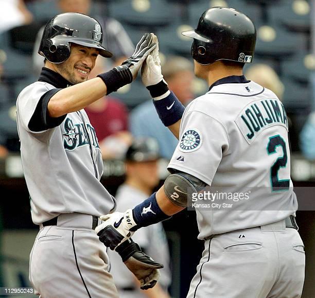 Seattle Mariners' Ichiro Suzuki left congratulates teammate Kenji Johjima after both scored on a tworun home run by Johjima in the eighth inning at...