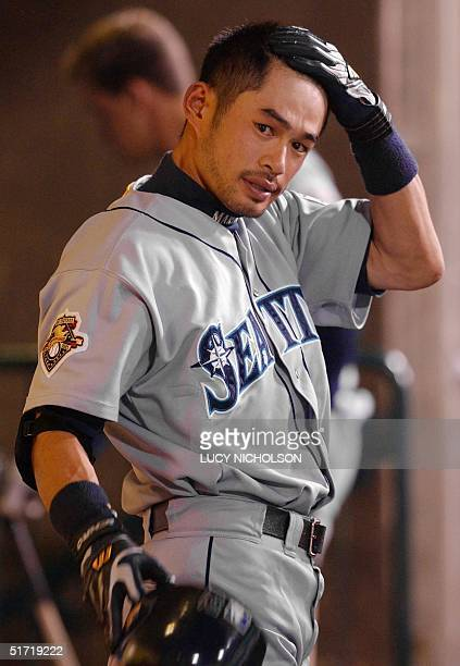 Seattle Mariners' Ichiro Suzuki puts on his helmet in the dugout before the start of the Mariners game against the Anaheim Angels in Anaheim CA 03...