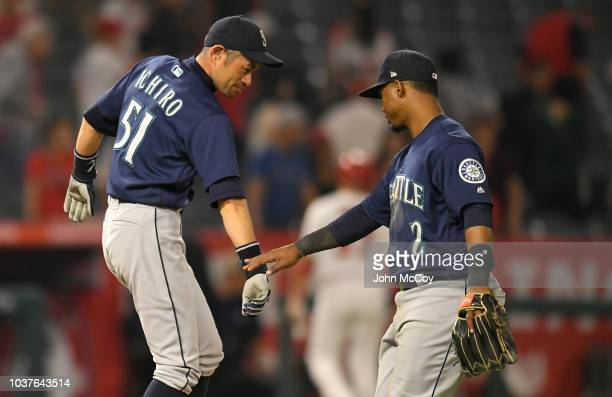 Seattle Mariners Ichiro Suzuki shakes hands with Jean Segura after the 50 win over the Los Angeles Angels of Anaheim at Angel Stadium on September 14...