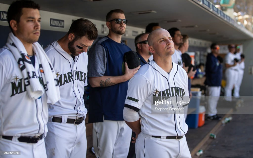 Seattle Mariners including Marco Gonzales #32 (L), Mitch Haniger #17 (2L) James Paxton #65 (3L) and Kyle Seager #15 stand in the dugout for a moment of rememberance at 3 p.m. local time during a game against the Texas Rangers at Safeco Field on May 28, 2018 in Seattle, Washington. The Mariners won the game 2-1. MLB players across the league are wearing special uniforms to commemorate Memorial Day.