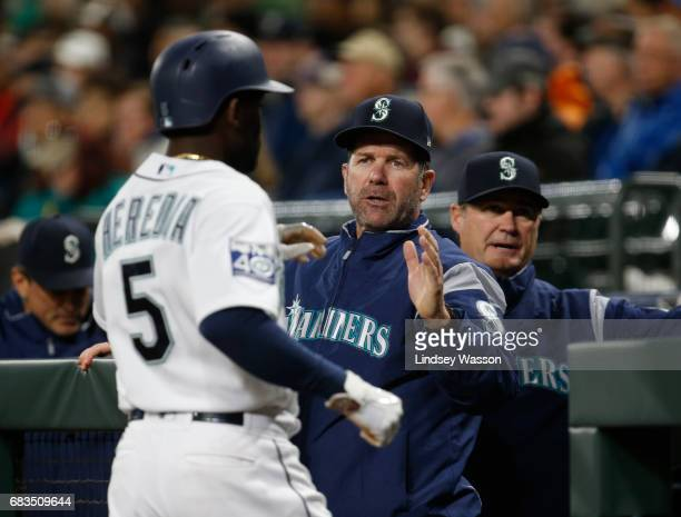 Seattle Mariners left fielder Guillermo Heredia is greeted by batting coach and former Mariner Edgar Martinez after scoring on a bases loaded walk in...