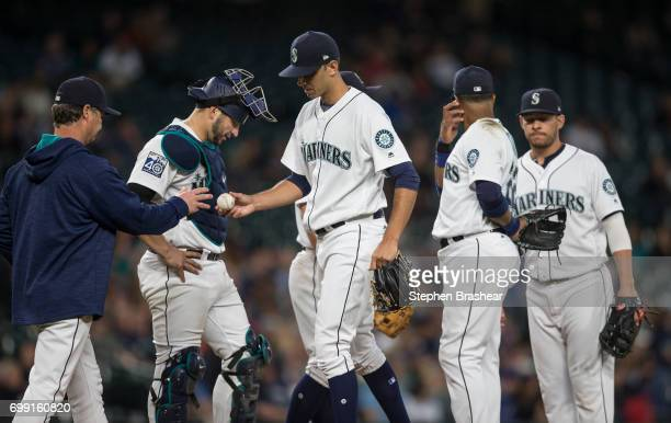 Seattle Mariners manager Scott Servais left pulls relief pitcher Steve Cishek center of the Seattle Mariners from a game against the Detroit Tigers...