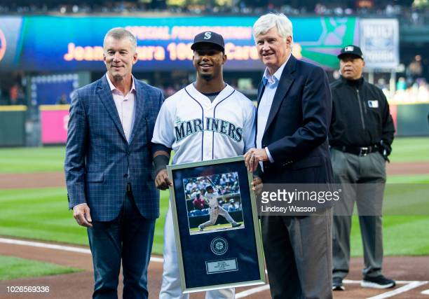 Seattle Mariners President Kevin Mather, left and CEO John Stanton pose with Jean Segura of the Seattle Mariners as he is presented with a plaque...