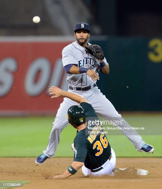 Seattle Mariners' Robert Andino top turns a double play as Oakland Athletics' catcher Derek Norris slides into second base out in the second inning...