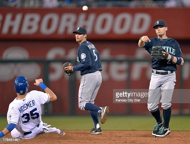 Seattle Mariners shortstop Brendan Ryan forces out Kansas City Royals' Eric Hosmer and steps to the side before throwing out Billy Butler at first...