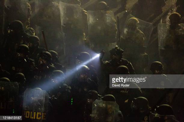 Seattle Police and Washington National Guard personnel retake control of an intersection as demonstrators clash with law enforcement near the Seattle...