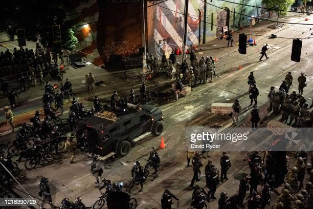 Seattle Police and Washington National Guard personnel take control of an intersection as demonstrators clash with law enforcement near the Seattle...