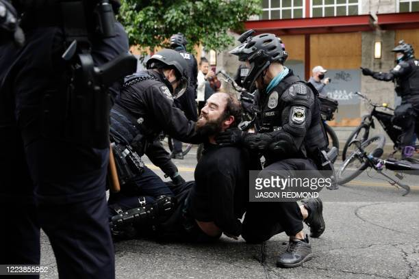 Seattle Police arrest a demonstrator who was blocking the intersection of East Pine Street and 11th Avenue after police cleared the Capitol Hill...